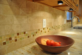 A photo of a Durango tiled backsplash with a kitchen counter made from River Gold granite